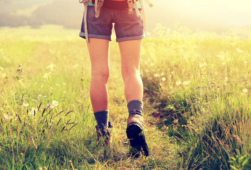 young woman in shorts hiking through field