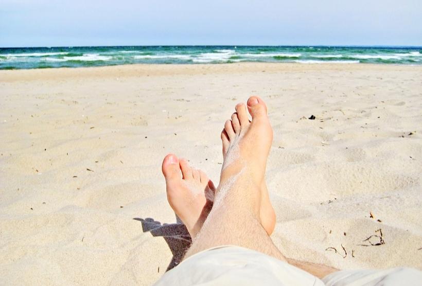 relaxed male feet on sandy beach