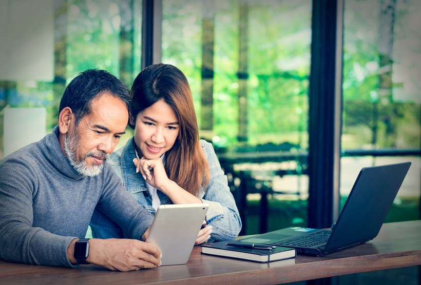 Attractive man looking at tablet with young woman