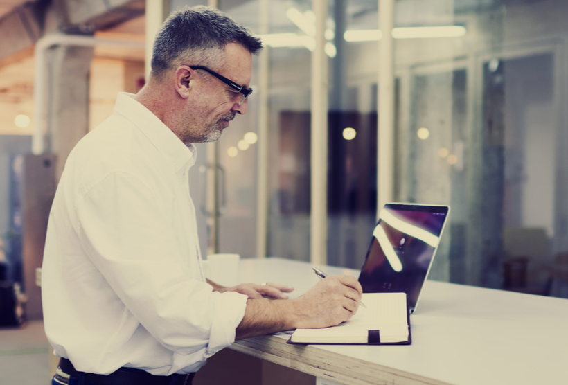 Businessman making notes in notebook and looking at laptop screen