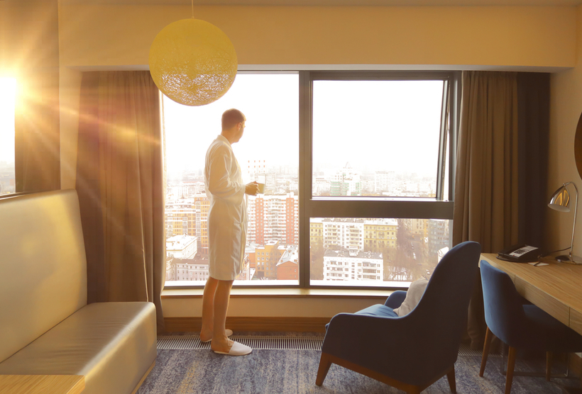 Man with morning coffee looks out of hotel window