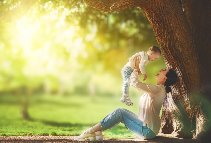 Mother and daughter playing under the tree on summer lawn