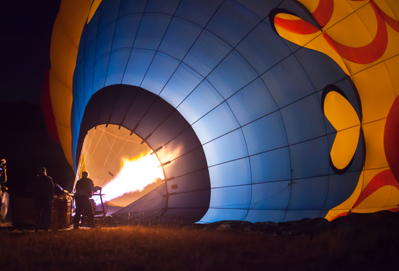A hot air balloon being hot air filled with flames before sunrise